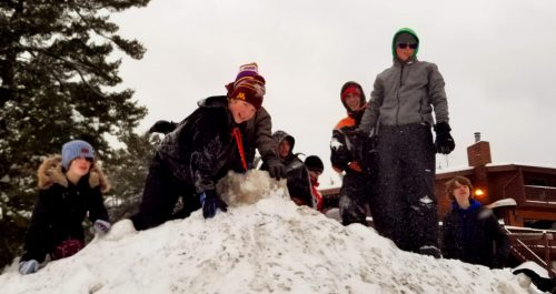 Members of DeMolay playing king of the hill on a snow pile